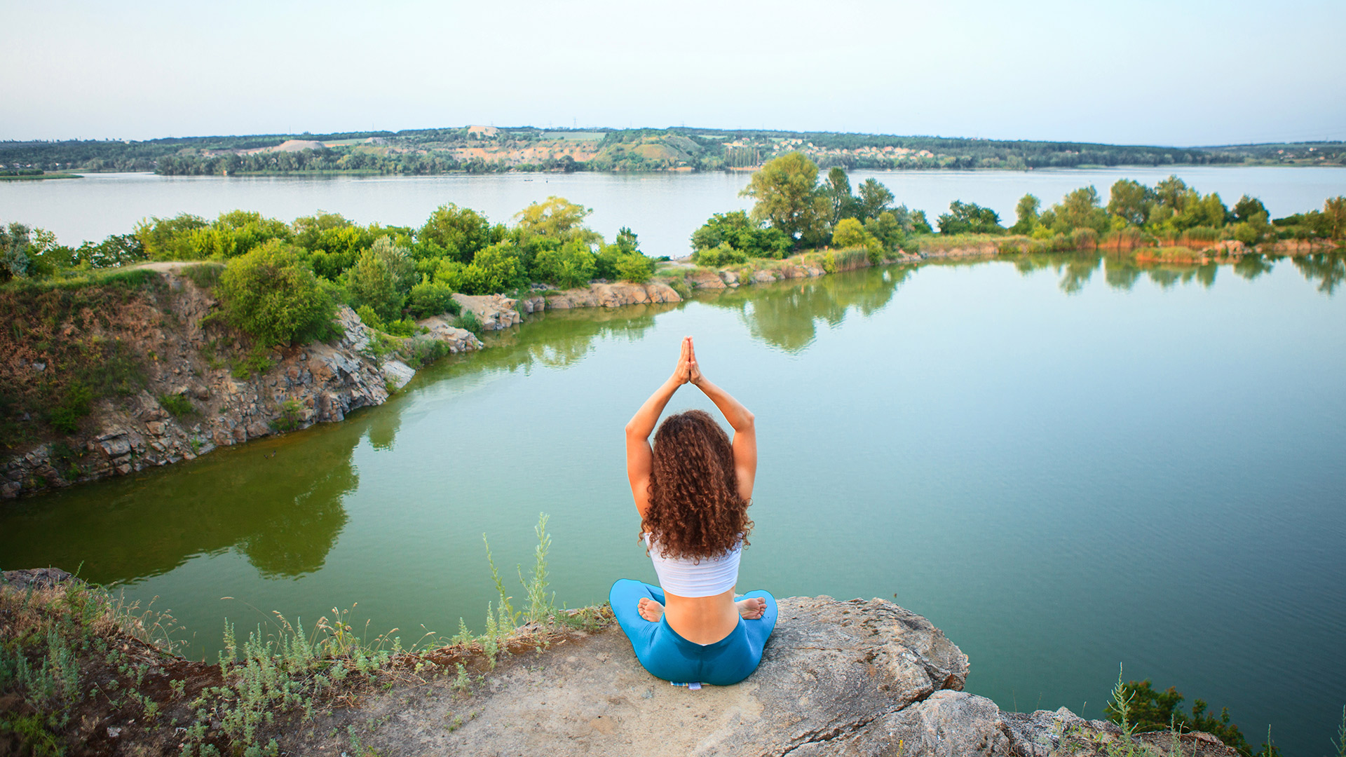 young-woman-is-practicing-yoga-near-river-PC3UBFL